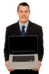Smart businessman displaying laptop to you
