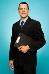 Corporate man holding clipboard and posing