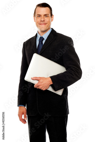 Handsome business executive holding laptop