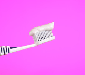 Toothbrush with Toothpaste on Pink Background