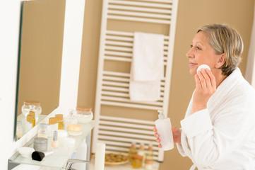 Senior woman bathroom clean face looking mirror