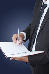 Businessman writing on notebook.