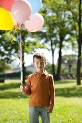 Little boy holding balloons
