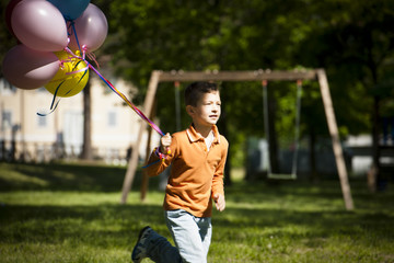 Little boy running with balloons