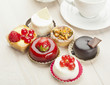 Different sort of beautiful pastry, small colorful sweet cakes