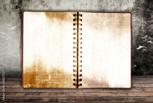 Grunge notebook on the wood wall.