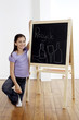 Girl holding a chalk with hand on the blackboard