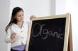 Girl looking at the word 'Organic' on the blackboard