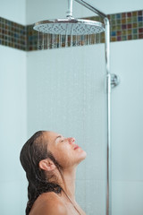 Woman with long hair taking shower under water jet