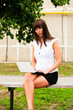 business woman sitting on a bench with a netbook