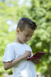 Little boy with handheld videogame outdoors