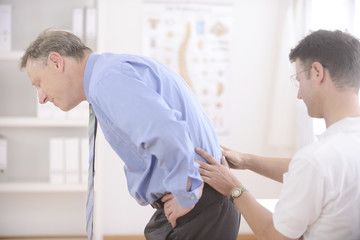 Chiropractic: Chiropractor examining senior man