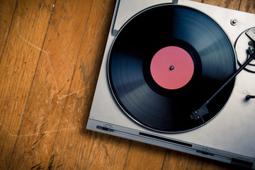 Vintage turntable with disc on wood