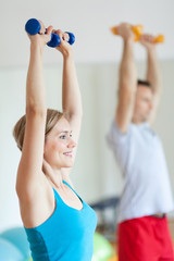 Couple in gym exercising with dumbbells