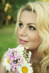 beautiful blonde woman with summer flowers outdoors