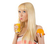 Pretty woman holding orange while sipping glass of juice