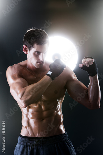 Muscular sports guy with a naked torso boxing