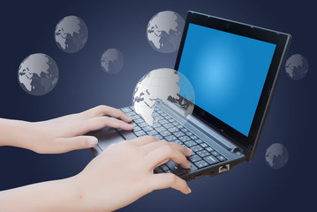Hand pushing laptop keyboard with globe.