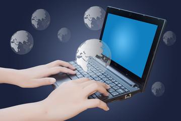 Hand pushing laptop keyboard with globe.