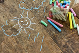 Child's drawings and coloured  chalk on wooden background