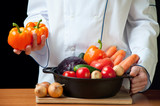 Food preparation: unrecognizable chef with variety of vegetables poster