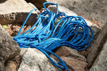 Outdoor shot of climbing rope lying on stones