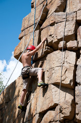 Vertical shot of a teenage rock climber stretching for hold