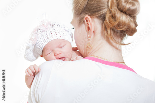 Young mother gently embraces the newborn child
