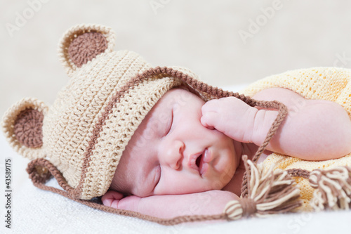 sleeping newborn baby with a ridiculous knitted hat
