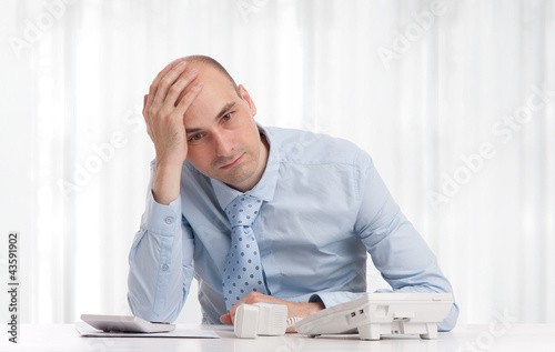 Stressed businessman sitting at workplace
