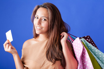 Beautiful shopping woman holding a credit card on blue backgroun