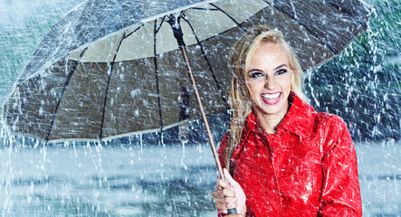 Beautiful blonde woman holding umbrella out in the rain