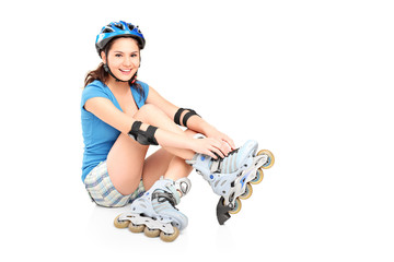 A girl putting on roller skates