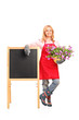 Female florist with flowers posing next to a board