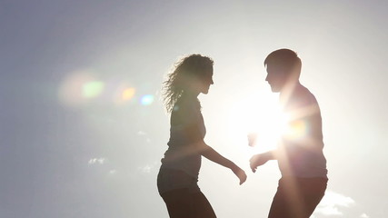 Silhouette couple dancing at the beach over sun
