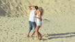 Attractive couple dancing on the sand together