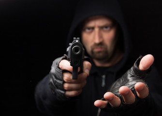 Robber with gun holding out hand