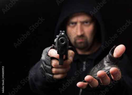 Leinwanddruck Bild Robber with gun holding out hand