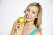 Attractive smiling young woman holding a green apple