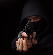 Masked robber with gun aiming into the camera