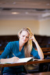 unhappy female college student studying in lecture hall