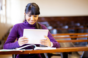 happy female indian college student using tablet computer