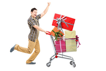 Full length portrait of a happy man pushing a shopping cart full