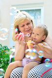 mother with baby blowing soap bubbles