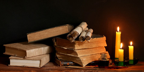 old books, scrolls, ink pen inkwell and candles
