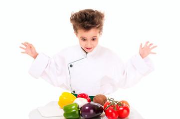 Little boy chef in uniform cooking vegatables