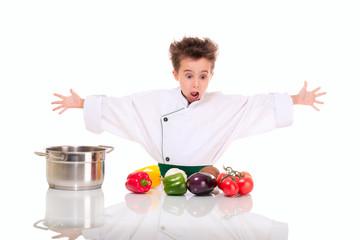 Little boy chef in uniform cooking vegatables shocked