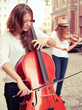 Two women strings duet playing violin and cello on the street