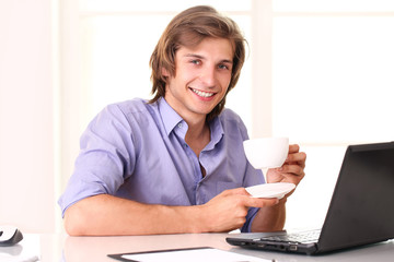 Young businessman taking a break with cup of coffee