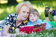 Senior woman reading book to her grandson